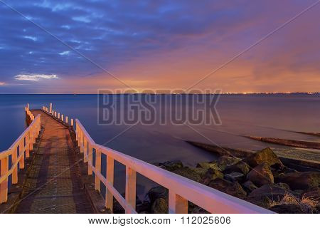 Small Jetty Leading Into The Sunset