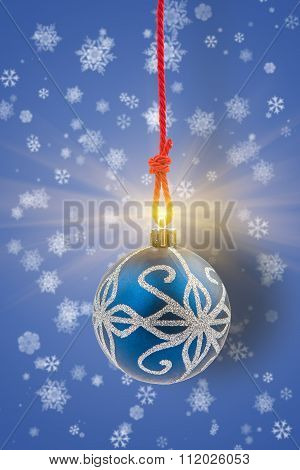 Christmas Bauble With Shining Light On Background With Snowflakes