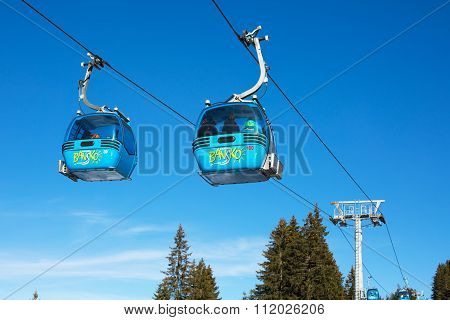 Close up Bansko cable car cabins, pine trees  against vibrant blue sky, Bulgaria