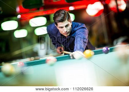 Young man playing pool in the bar