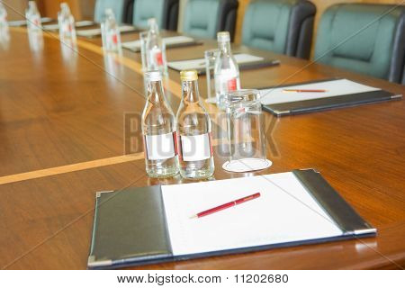 Table With  Block-notes And Bottles Of Water