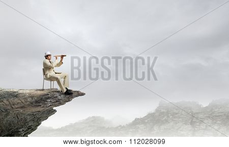 Businessman in white suit and hat sitting in chair and looking in spyglass