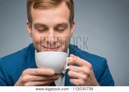 Handsome businessman enjoying his coffee.