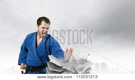 Young determined karate man breaking with hand concrete bricks