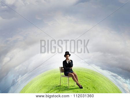 Pretty girl wearing retro hat siting on chair