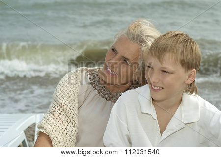 elderly woman with grandson on beach