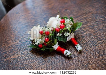 Buttonhole With Red Ribbons On Wodden Table