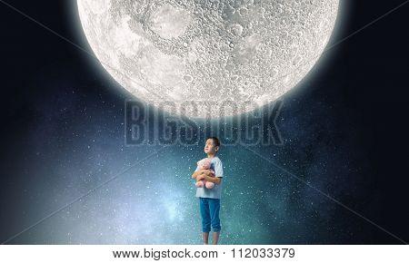 Cute little boy with toy bear in night darkness