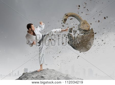 Young determined karate man breaking with anger concrete lock