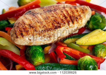 Grilled chicken fillet, breast with cooked vegetable  on plates.