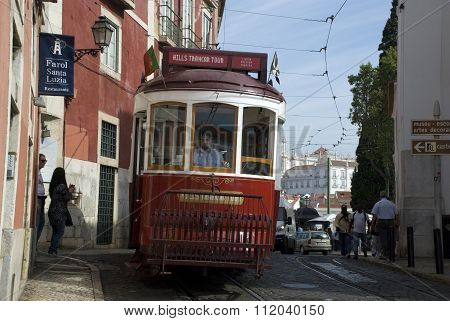 Lisbon, Portugal - September 2015: a red tourist tram of Lisbon on its way through the Alfama, Portugal, in September 2015, with people on the pavements and in the tram