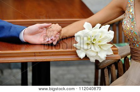 Hands Of The Bride And Groom On The Background Of A Wedding Bouquet Callas