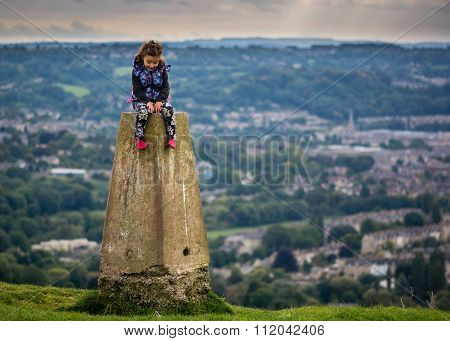 Young girl sitting on triangulation point on Little Solsbury Hill, Bath, UK