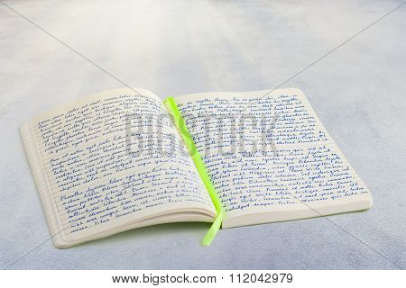 Open Notebook With Handwritten  Lorem Ipsum Text And Ribbon Bookmark In The Middle