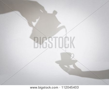 Delicate Shadows Of Coffee Pot Pouring Coffee Into A Cup Held By Female Hand