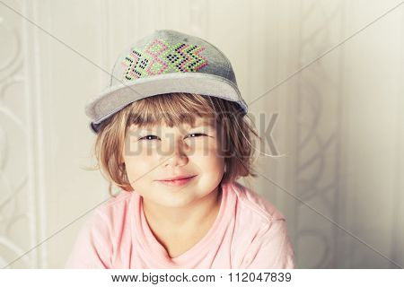 Portrait Of Smiling Cute Blond Baby Girl In Gray Cap