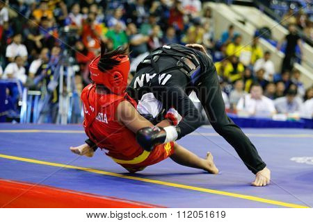 JAKARTA, INDONESIA - NOVEMBER 18, 2015: Moria Manalu of Indonesia (red) fights Sedigheh Dariaeivarkadeh of Iran (black) in the women's 60kg Sanda finals at the 13th World Wushu Championship 2015.