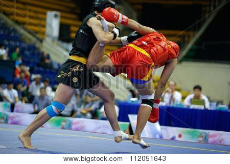 JAKARTA, INDONESIA - NOVEMBER 18, 2015: Pooja Kadian of India (red) fights Yuan Li of China (black) in the women's 75kg Sanda event finals at the 13th World Wushu Championship 2015 in Jakarta.