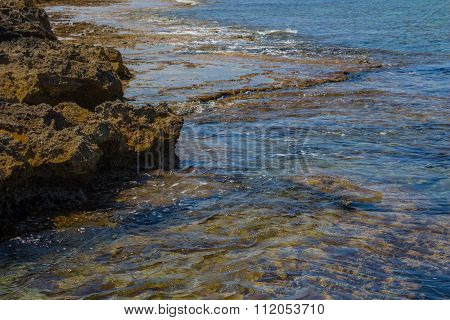 Transparent Sea Waves On A Rocky Beach.