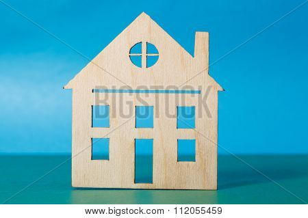 Small Wooden House On Blue Background