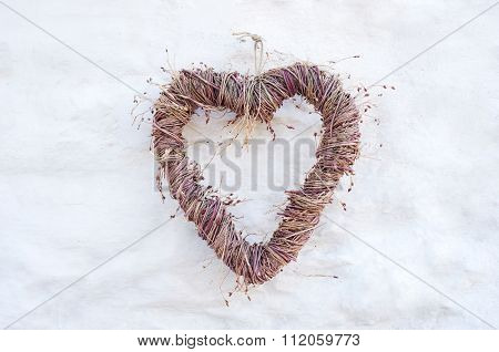 Rustic heart shape made from twig branches hanging on farmhouse country whitewash brick wall, background for wedding invitation or card