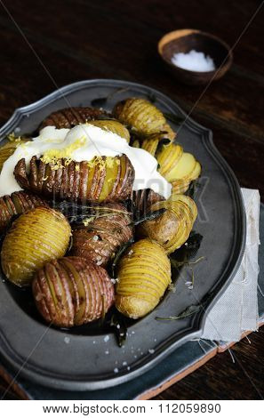 Roast potatoes with fresh herbs, lemon zest and sour scream on vintage platter styled by food stylist
