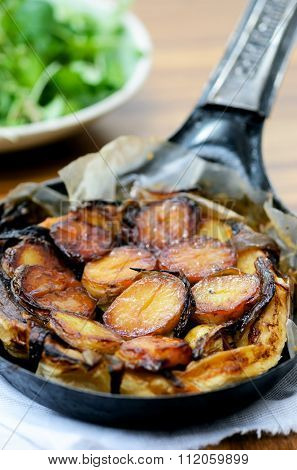 Potato Tarte Tatin in individual pan with ingredients out of focus, styled by professional food stylist
