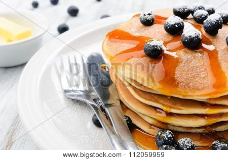 Delicious pancakes stack with fresh blueberries and flowing dripping maple syrup