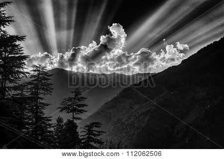 Sun rays over mountains. Black and white