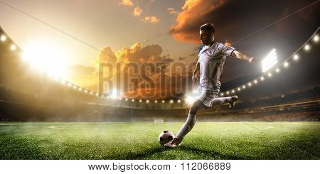 Soccer player in action on sunset stadium panorama background