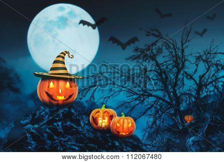 Helloween pumpkins with candles in the night forest