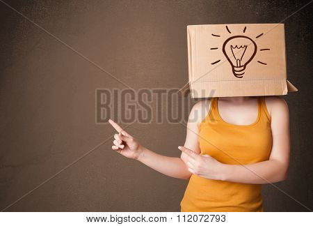 Young woman standing and gesturing with a cardboard box on her head with light bulb