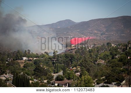 Rancho San Diego, June 19, 2015.  Firefighting plane discharging fire retardant chemical to put out a fire.