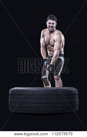 Sportsman hammering a tire isolated on black