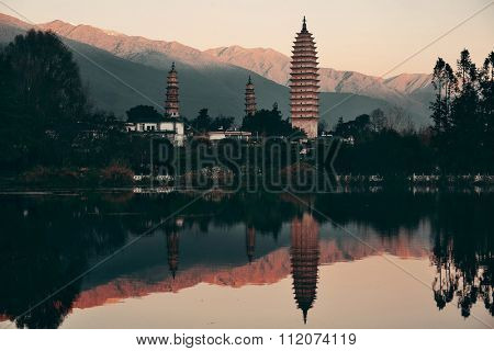 Ancient pagoda in Dali old town with lake reflection at sunrise, Yunnan, China.