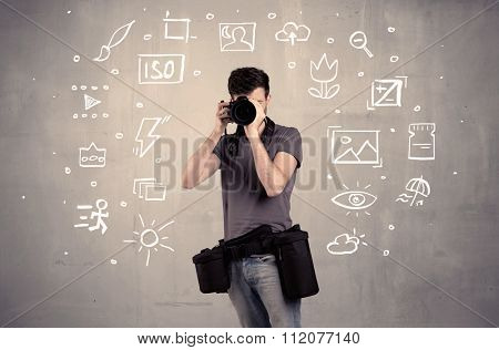 An amateur hobby photographer learning to use a professional digital camera with camera settings icons on the background wall concept