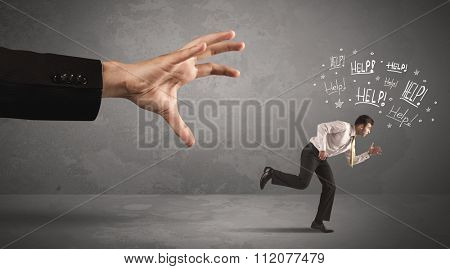 Business person running away from big hand while asking for help concept on background