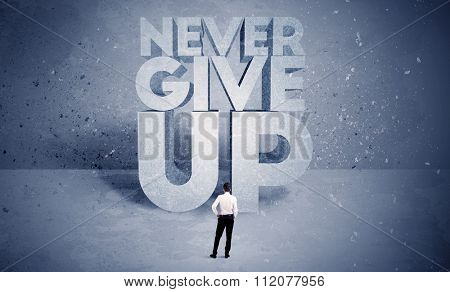 A stressed out business worker standing in front of huge block letters saying never give up in blue open environment concept