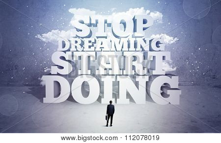 A lazy sales person standing in emty space with huge block letters illustration saying stop dreaming start doing and clouds concept