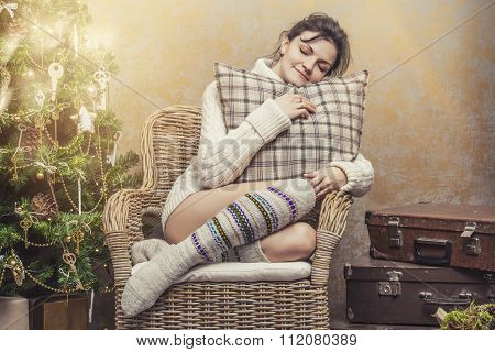 Beautiful Woman Relaxing Sitting In A Chair In The Christmas Interior