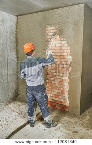 Plasterer operating sprayer equipment machine for spraying thin-layer putty plaster finishing on brick wall