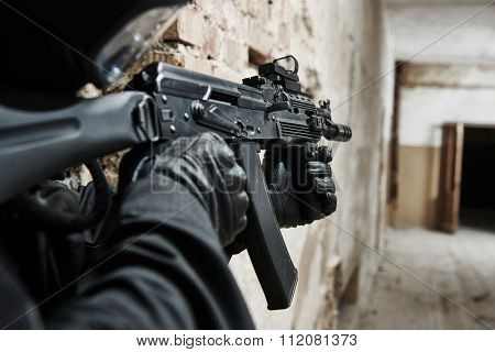 military industry. special forces or police soldier, private contractor armed with assault rifle ready to attack during clean-up operation, mission