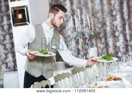 Waiter occupation. Young man with food on dishes servicing during catering in restaurant