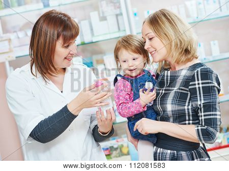pharmacist chemist woman demonstrating cream gel to child girl with mother in pharmacy drugstore. family health