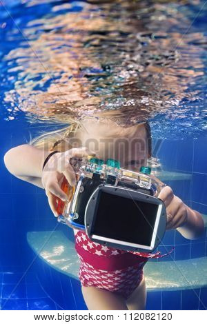 Little Child With Camera Takes Underwater Photo In Pool.