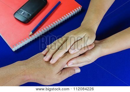 Women And Man Hold Hands On Table