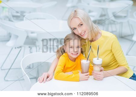 Happy mother and daughter sitting in the cafe