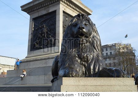 LONDON, UK - DECEMBER 19: Detail of one of the four lions statues that surround Nelson's Column in Trafalgar Square, with children seated in the background. December 19, 2015 in London.