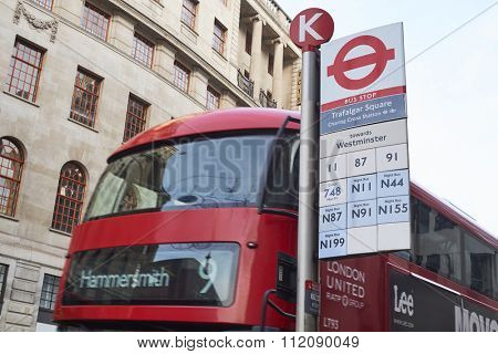 LONDON, UK - DECEMBER 19: Detail of Strand street sign with cropped double-decker red buses in the background. December 19, 2015 in London.