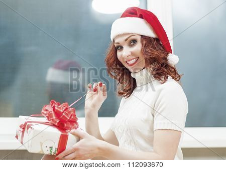 Christmas And New Year Celebration And Holiday Concept. Cacasian Red-haired Santa Girl Unwrapping Gi